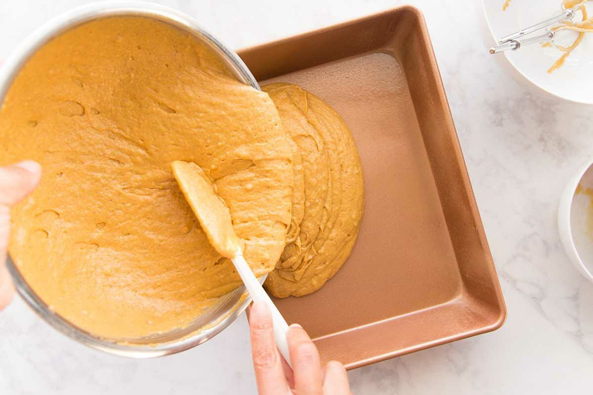 Batter for The Best Pumpkin Cake with Cream Cheese Frosting being poured into a cake pan.