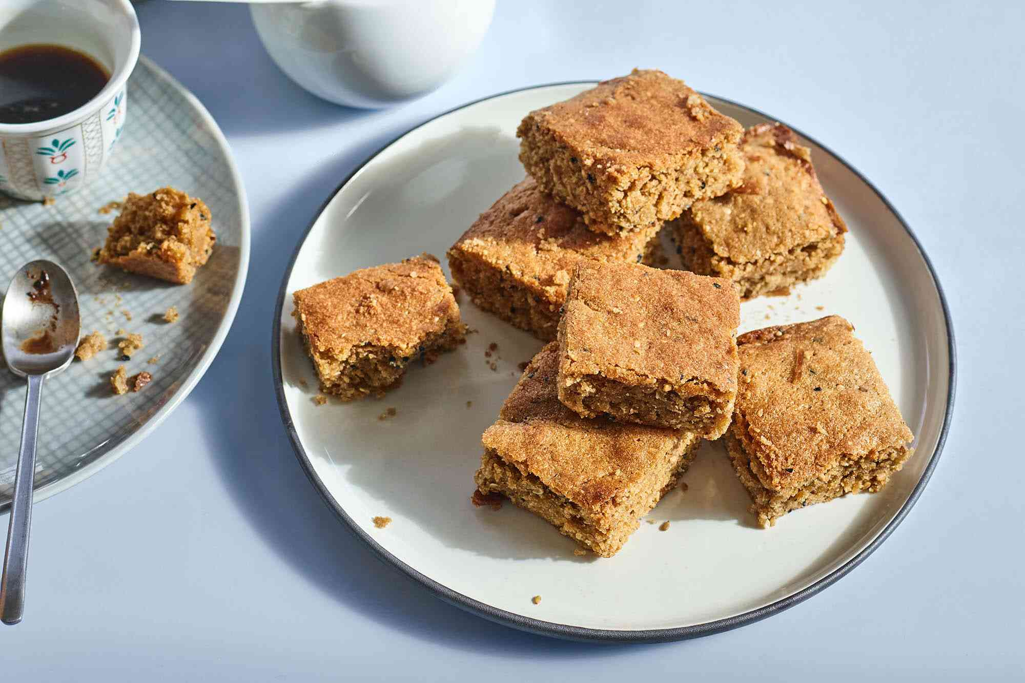 White plate with a stack of square cute chewy tahini blondies on it against a bluish grey background. A cup of coffee with a partially eaten blondie is nearby.