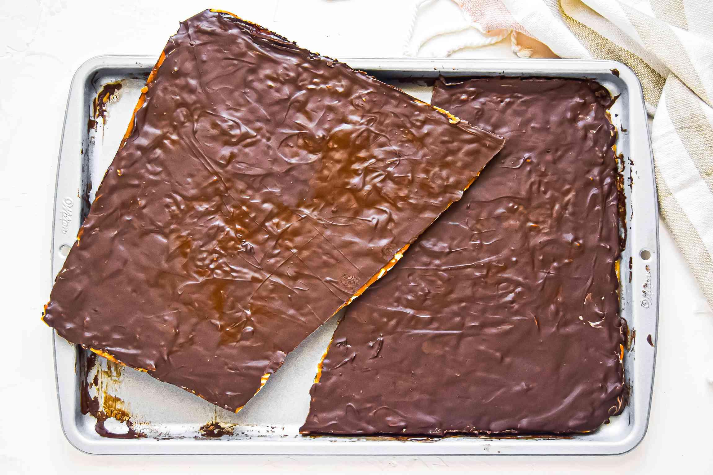 A large sheet of almond roca split in half on top a baking sheet.