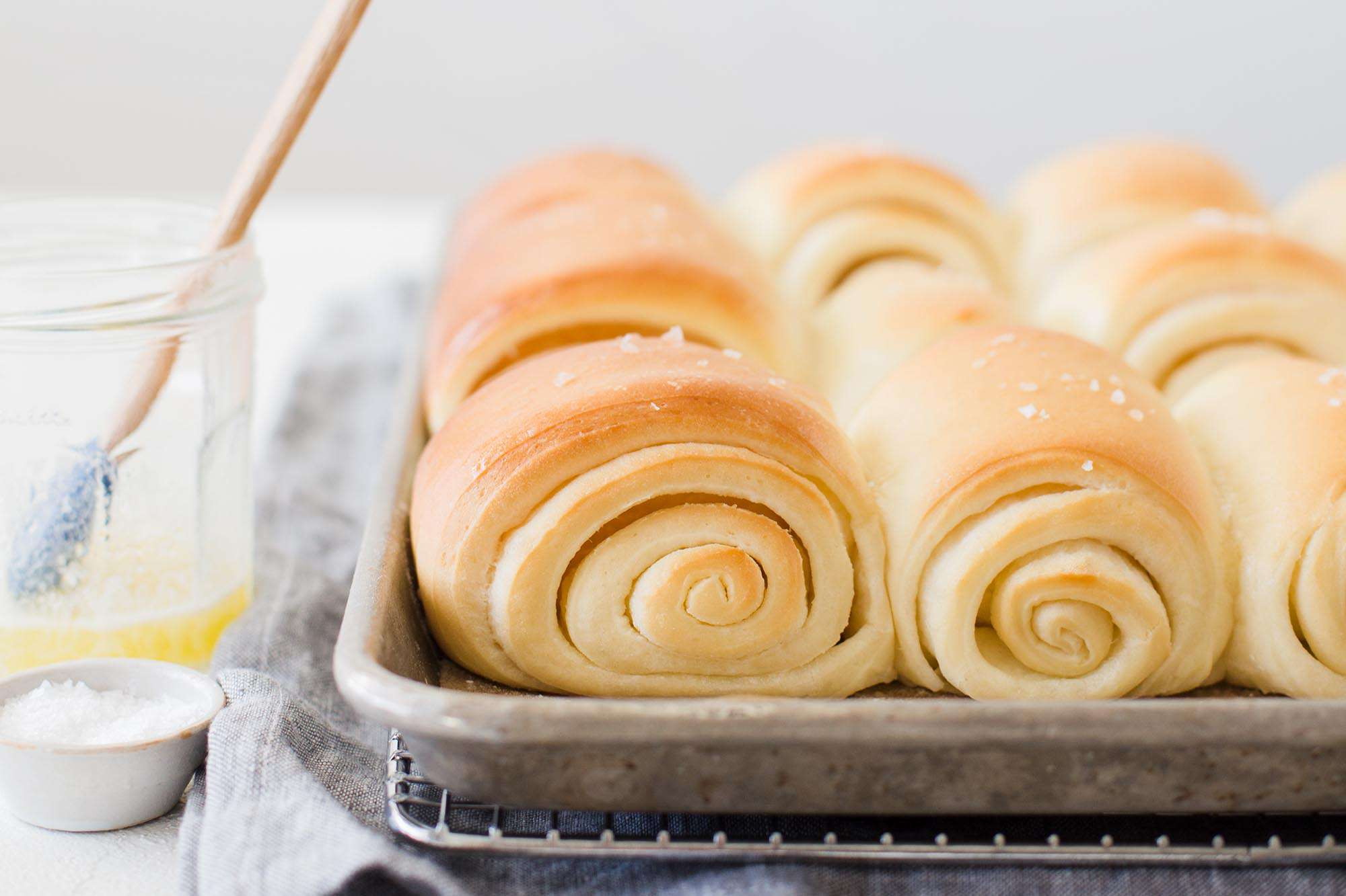Utah's famous lion house rolls on a baking sheet with a jar of melted butter to the left.