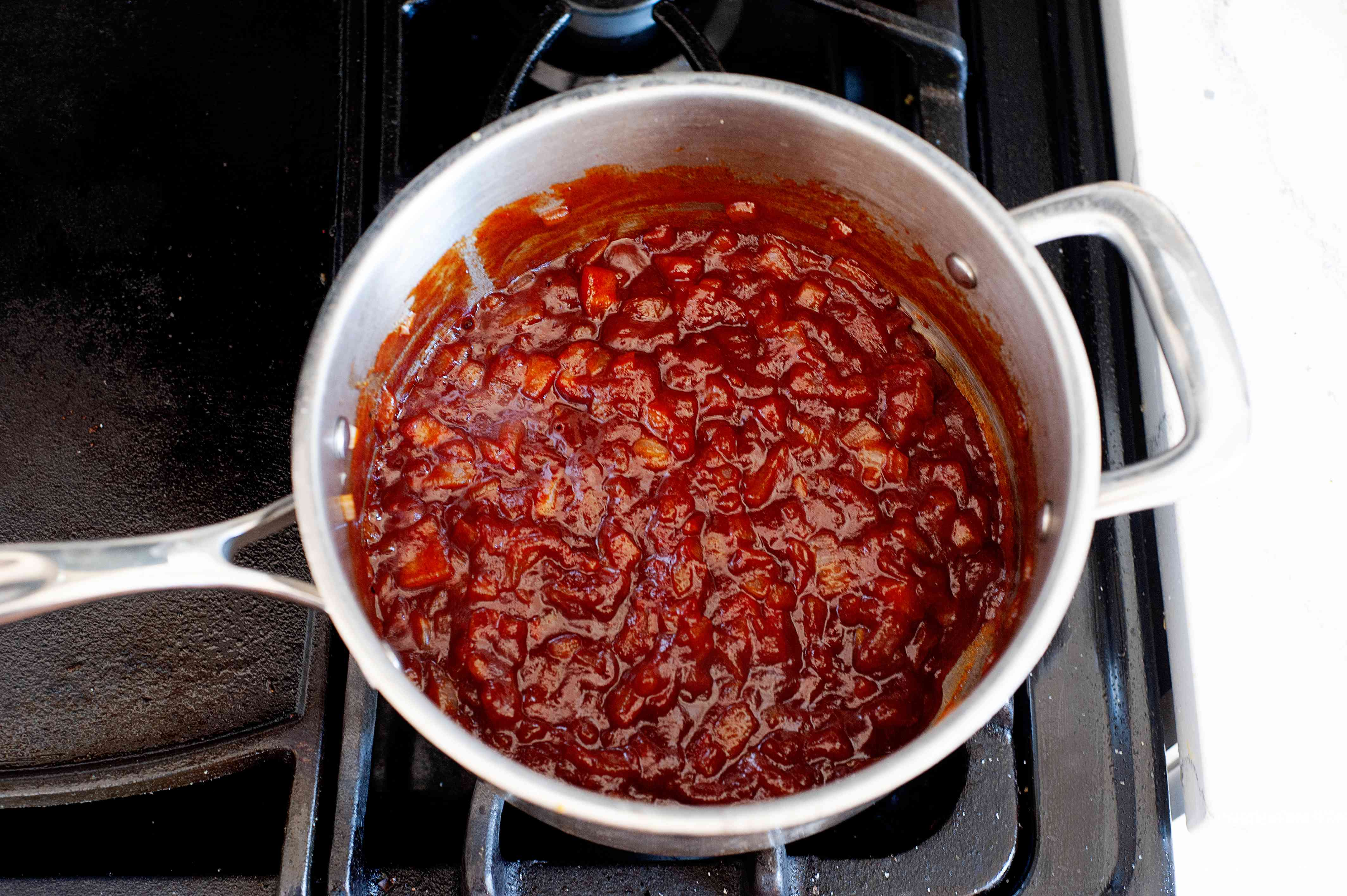 Cooking easy homemade ketchup in a pot.