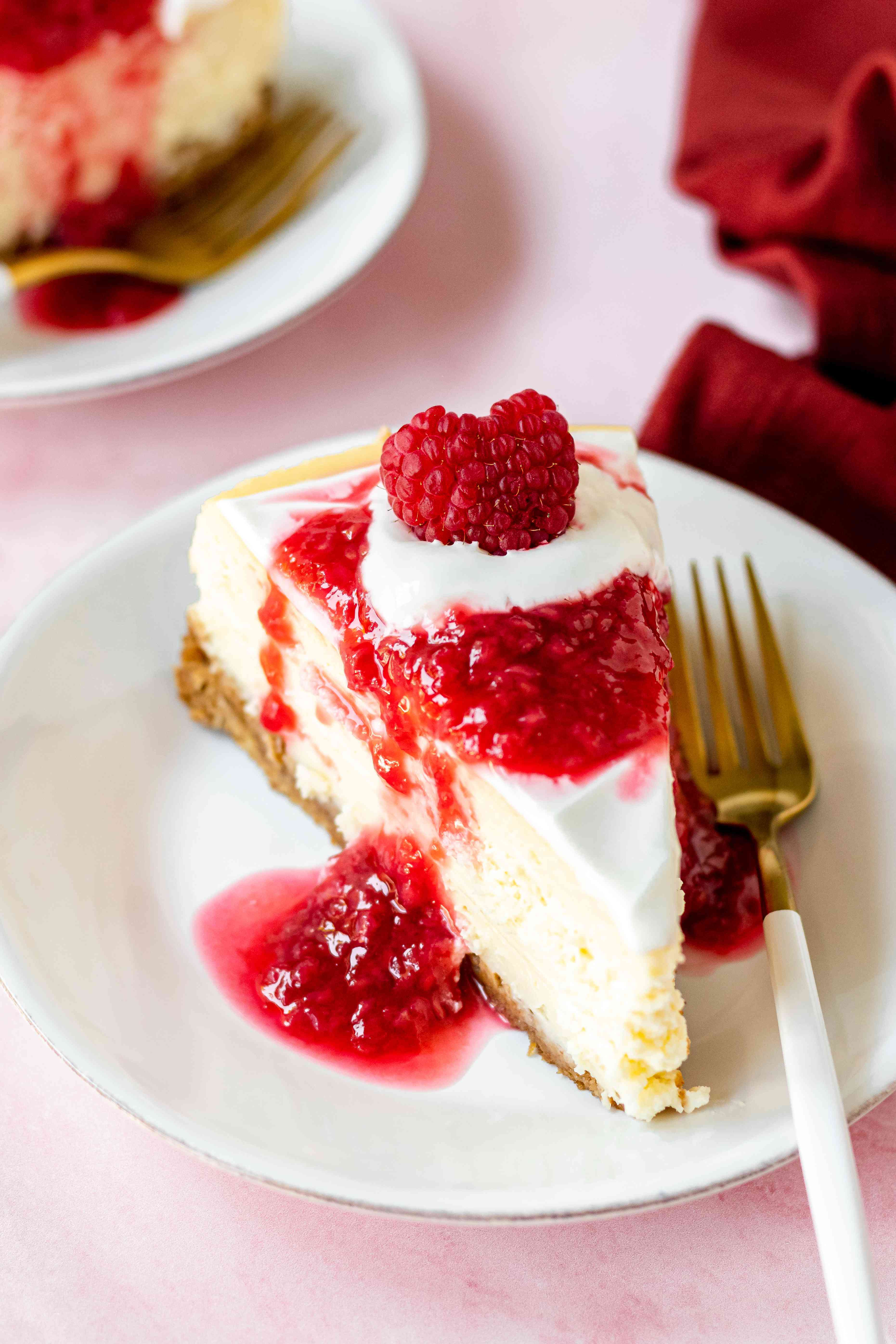 A slice of homemade cheesecake topped with raspberry sauce and on a plate with a fork.