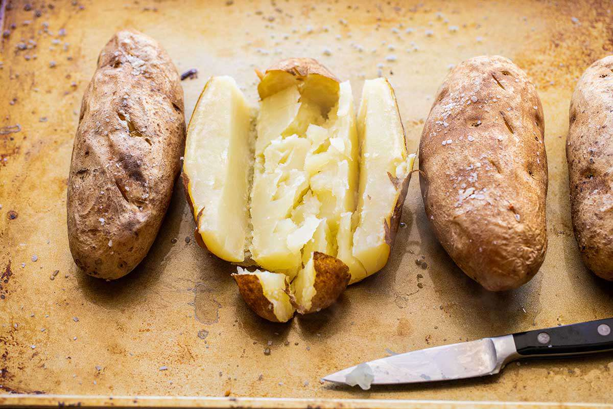Four baked russet potatoes are on a worn baking sheet. The skin is salted and a paring knife is laid underneath the potatoes. One potato is cut down each side and across the top revealing the creamy potato inside.