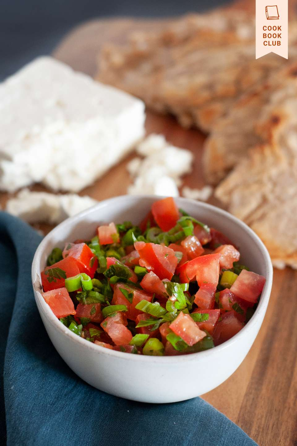 Side view of Lasary Legioma (Tomato Relish) in a white bowl set on a wooden board.