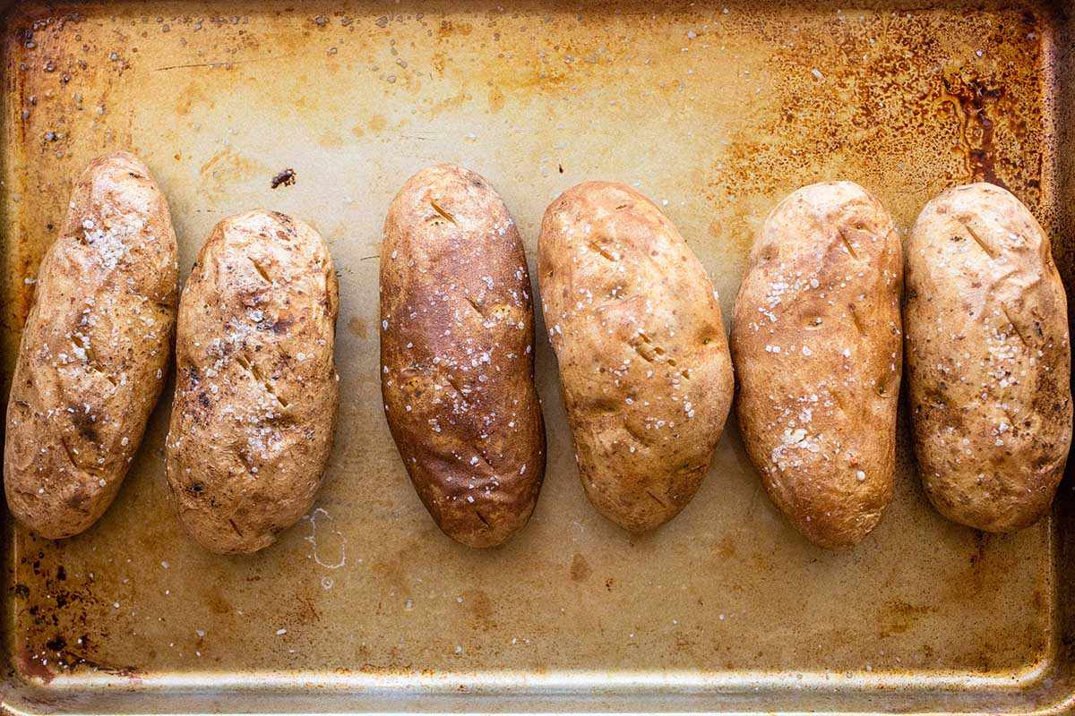 Six russet baked potatoes are on a worn baking sheet. The skin is dimpled and salt covers each one.
