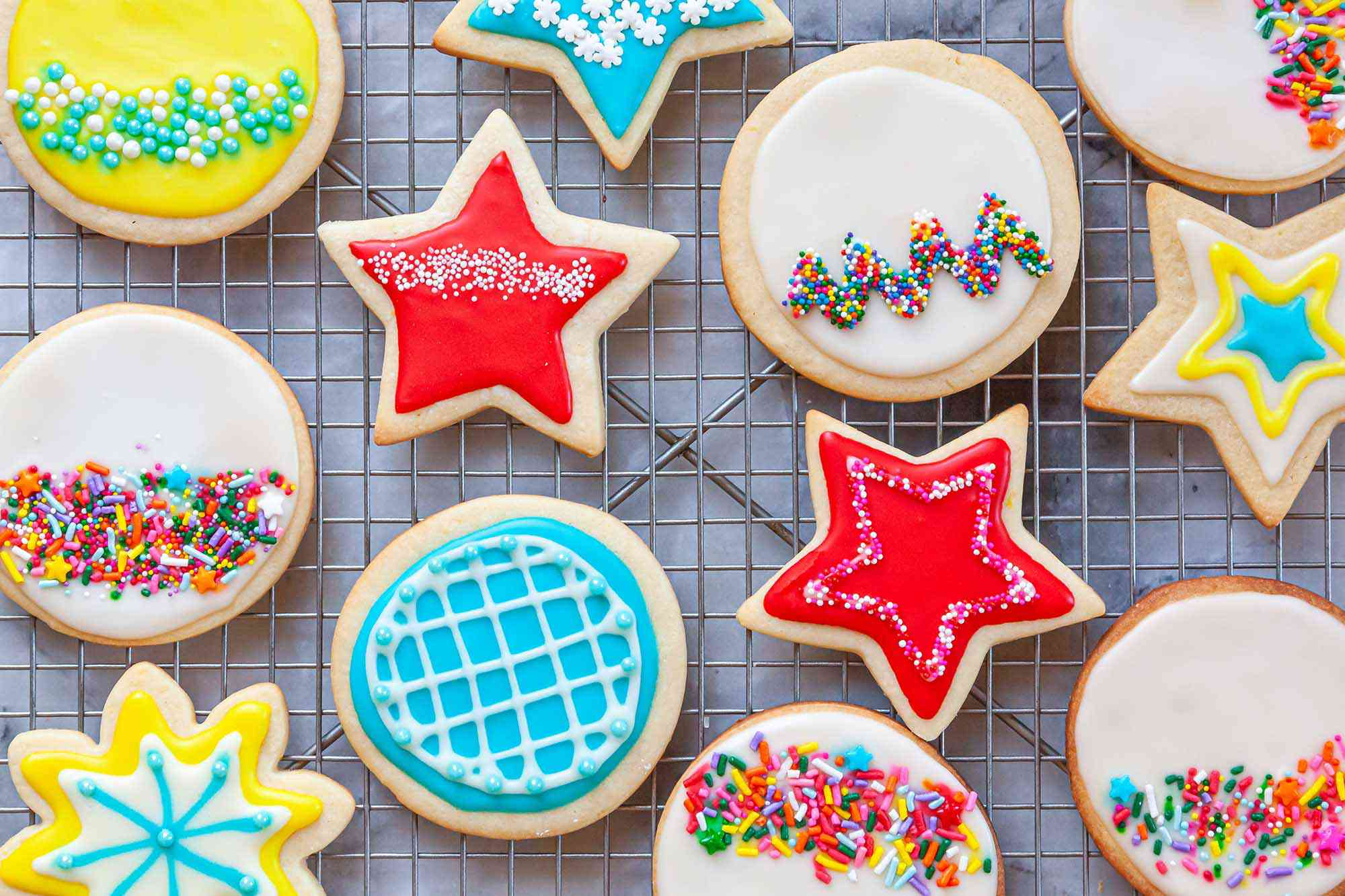 Royal icing for sugar cookies piped into a variety of patterns and sent on a cooling rack.