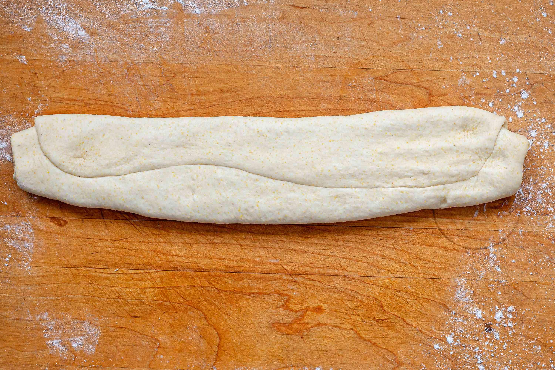 Dough to make Italian Sausage Deep Dish Pizza on a cutting board.