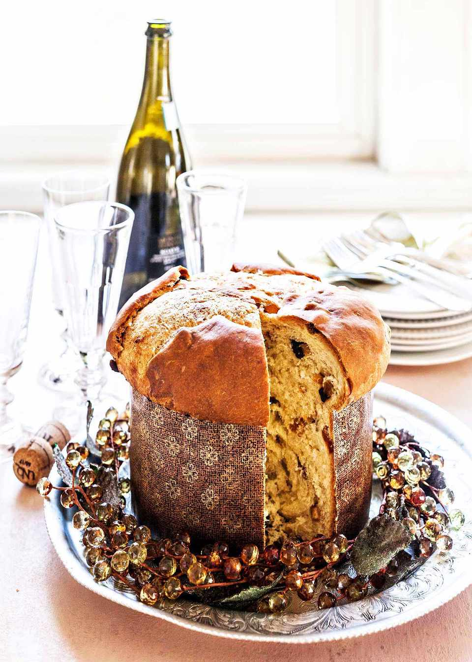 A loaf of homemade panettone in a paper mold with a slice cut out with a bottle of wine, and glasses in the background.