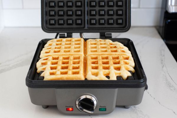 Front view of an open waffle maker with a cooked waffle inside and the red