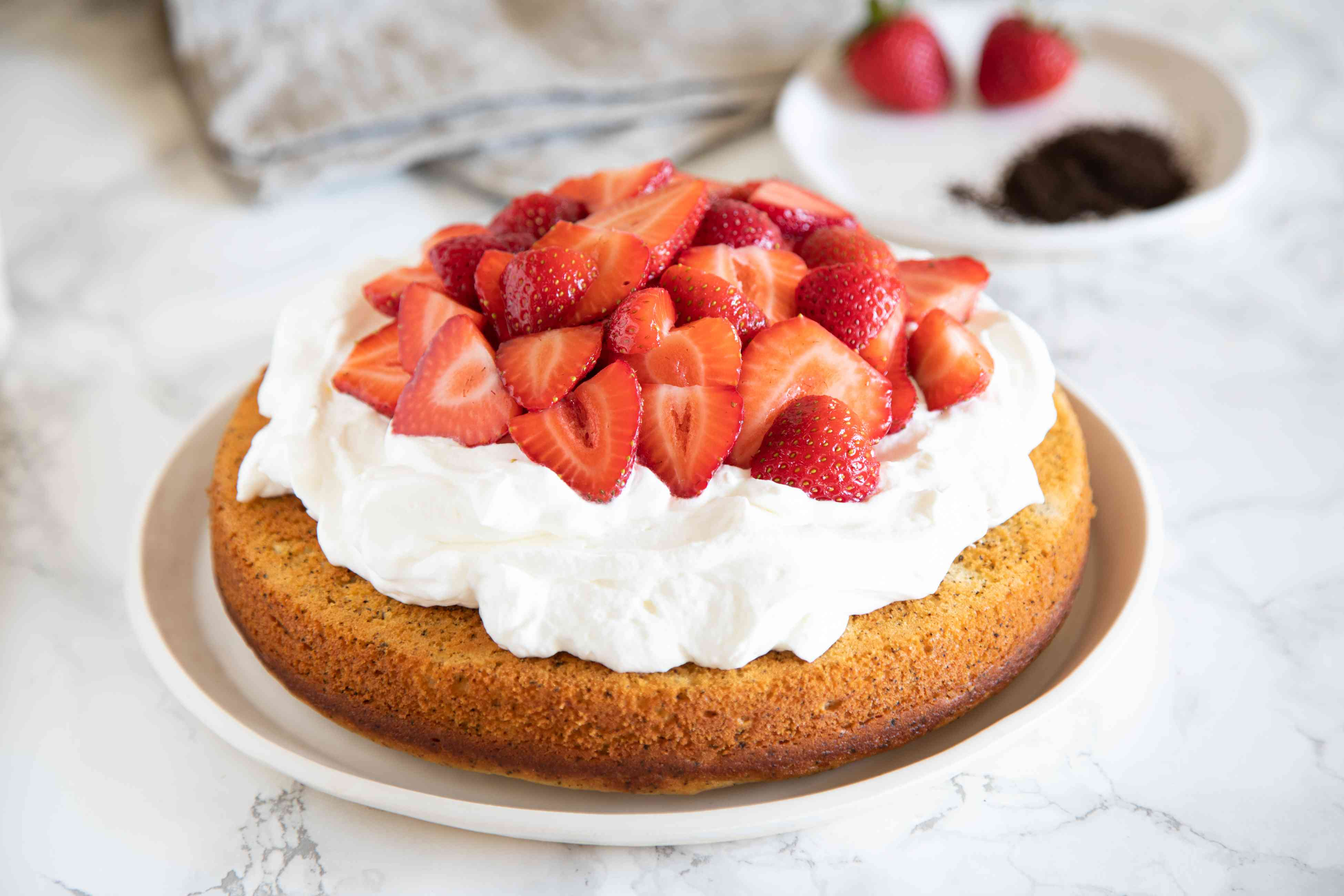 Earl Grey Yogurt Cake on a white platter and topped with whipped cream and strawberries.
