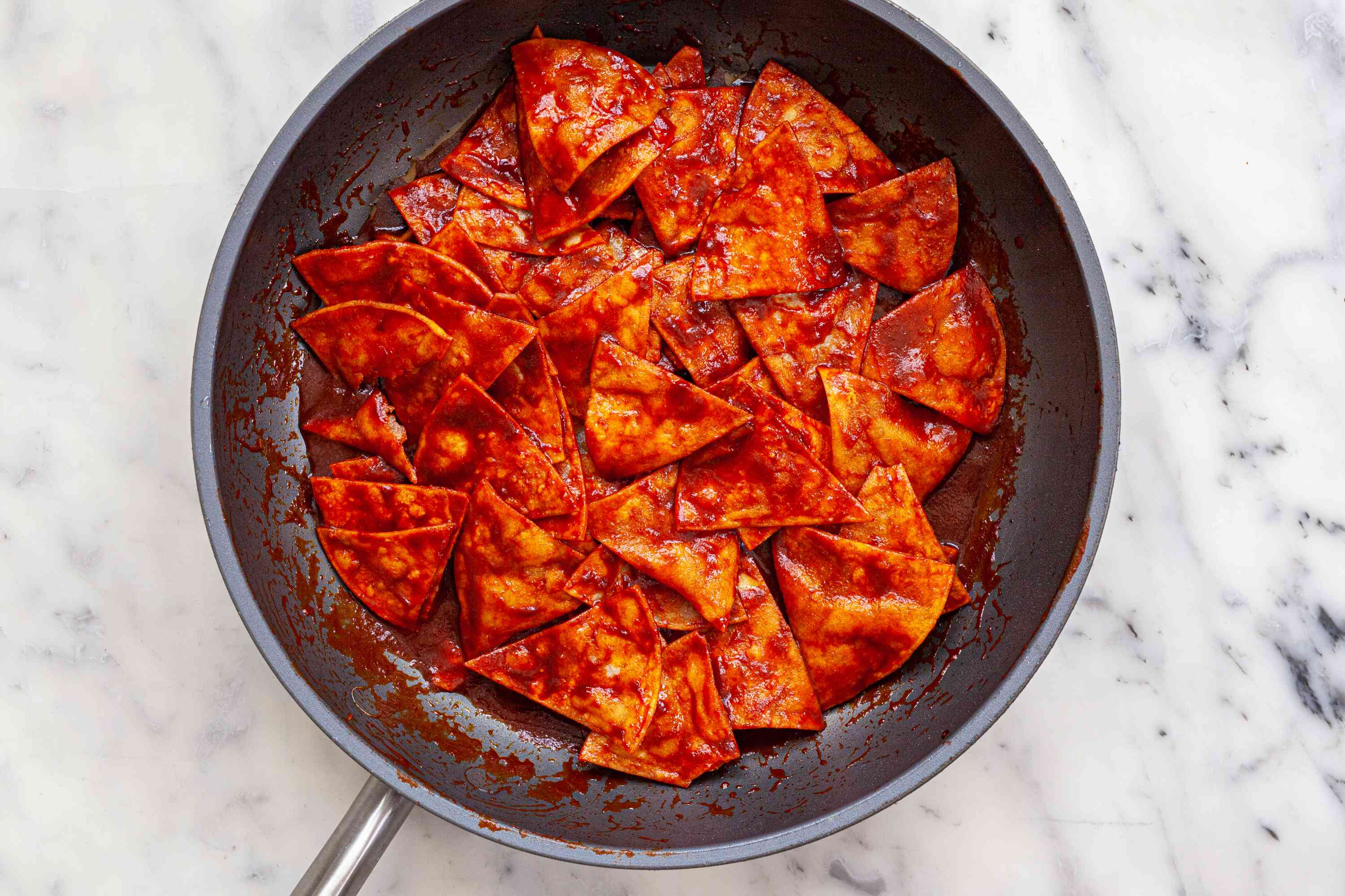 Chips and sauce in a skillet to show how to make chilaquiles.