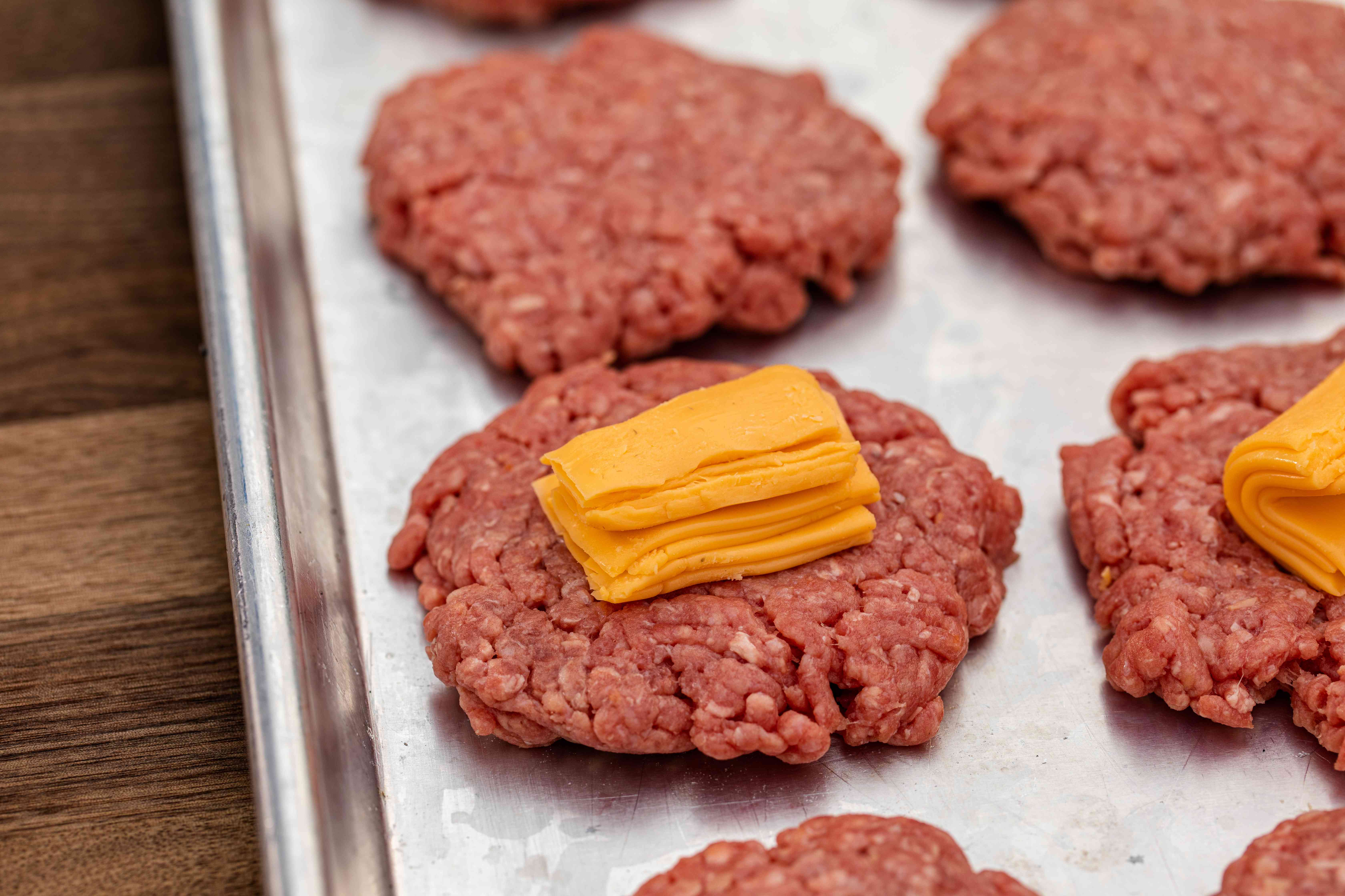 Folded sliced cheese on top of burger patties to show how to make a Jucy Lucy burger
