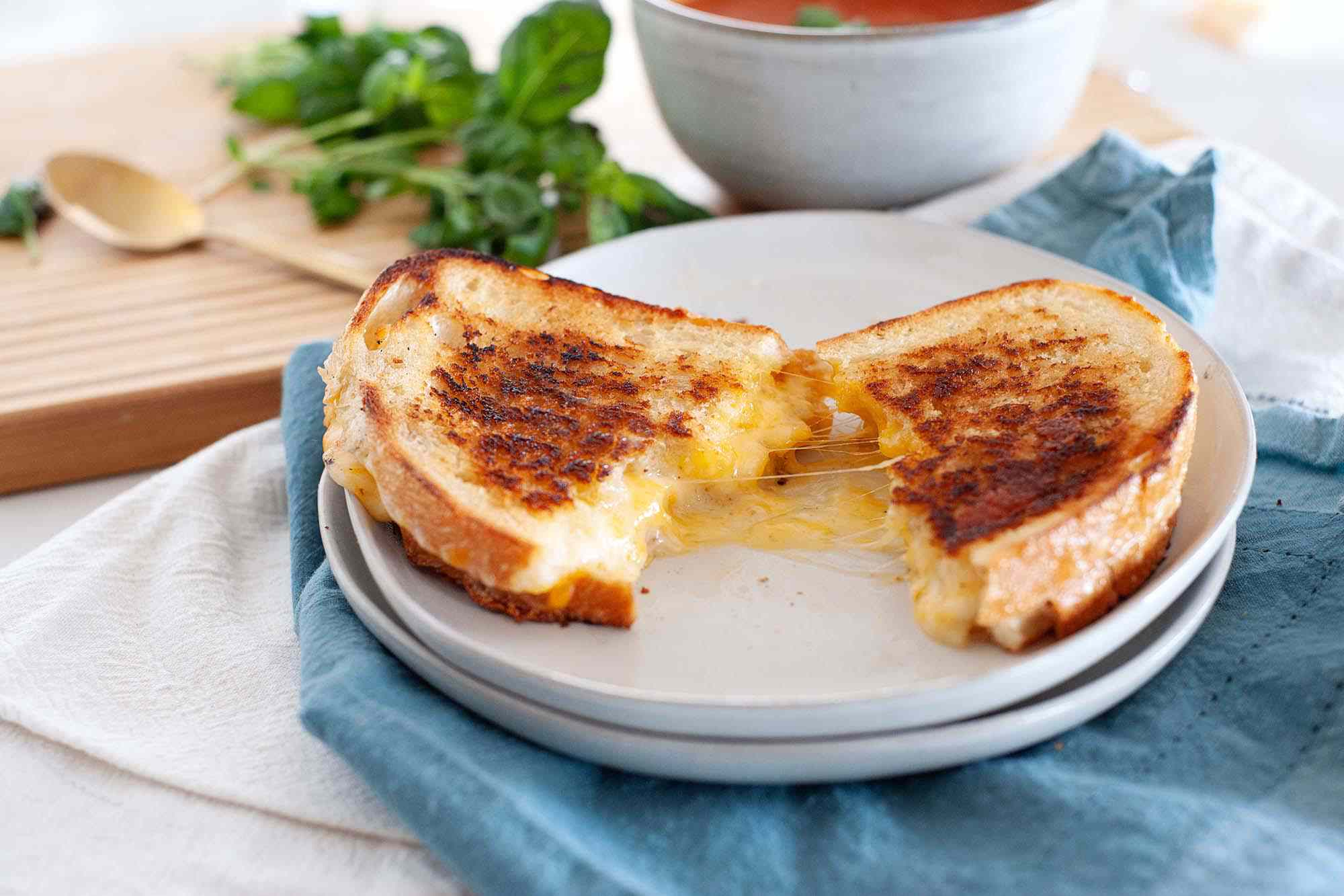 The perfect grilled cheese sandwich cut in half and split open on a plate with a blue napkin underneath it and a bowl of tomato soup in the background.