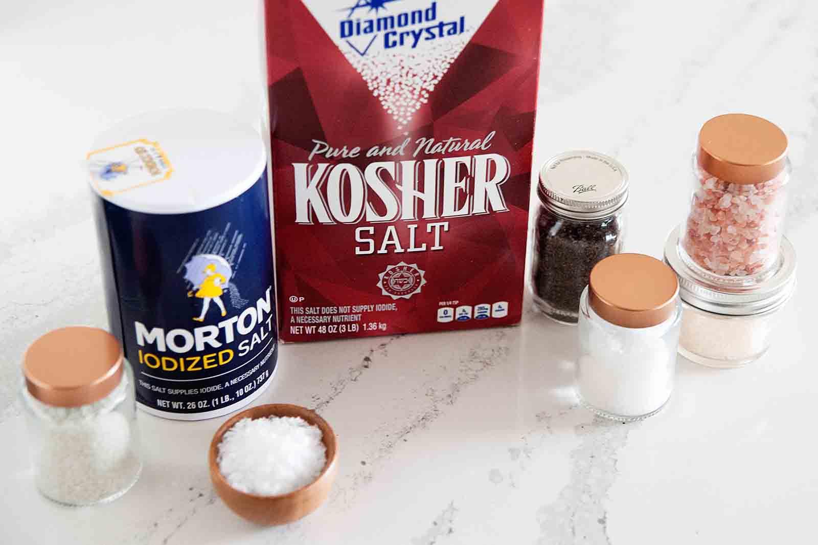 Boxes of Diamond Kosher Salt, Morton Idoized salt and jars of smoked salt, and Maldon salt