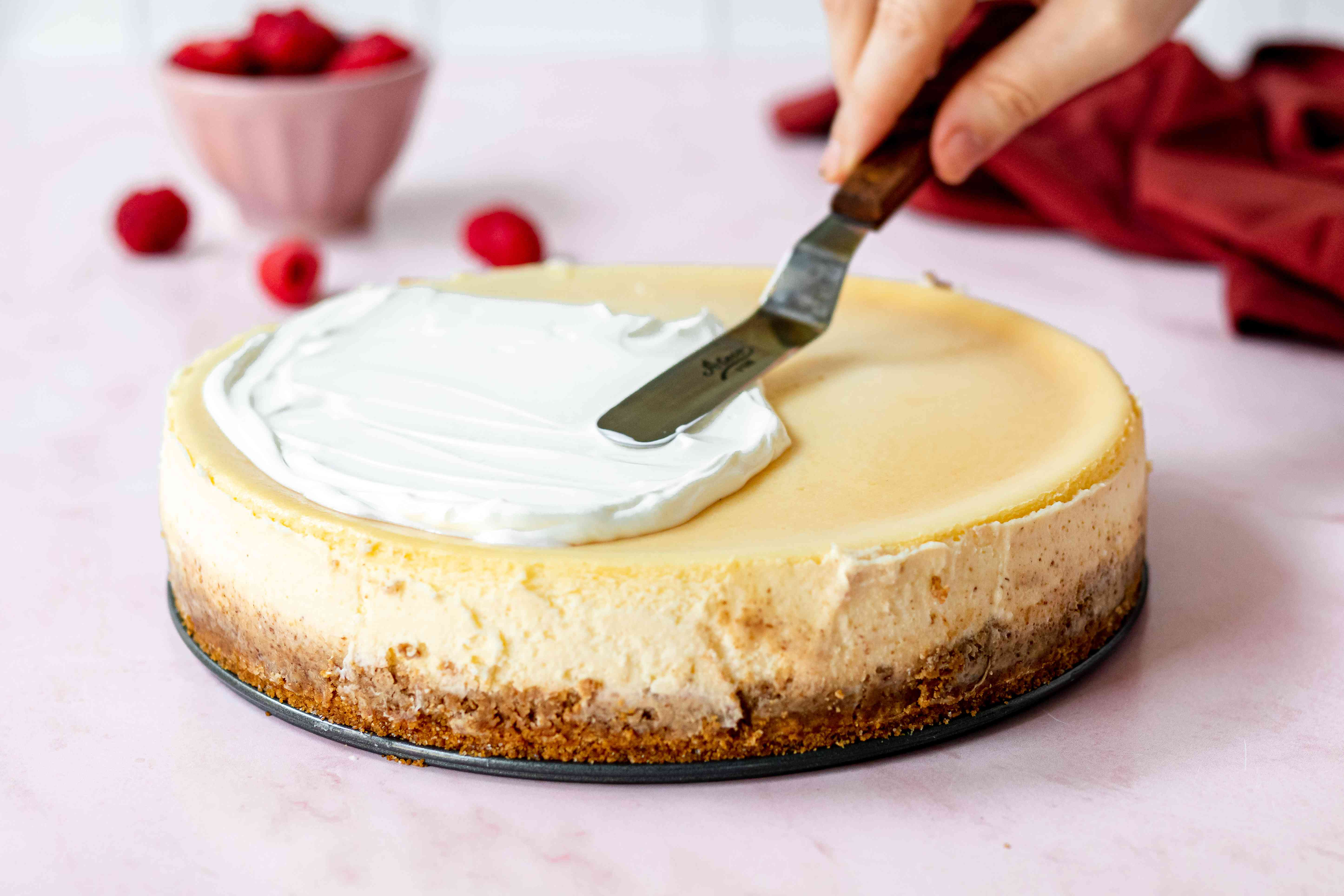 Spreading the cheesecake with a sour cream topping.