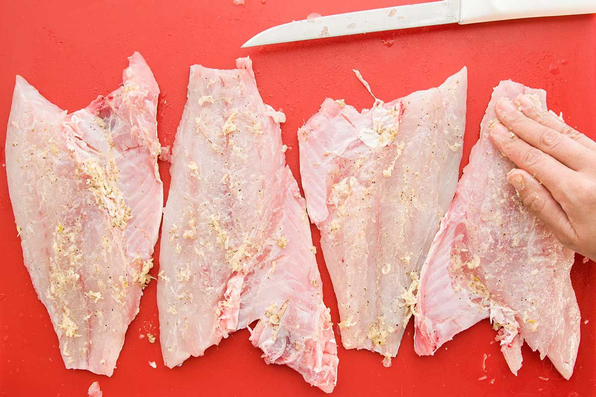 Four raw fillets of red snapper is being coated by hand with a garlic marinade. They sit on a red cutting board and a knife is laid above the fillets.