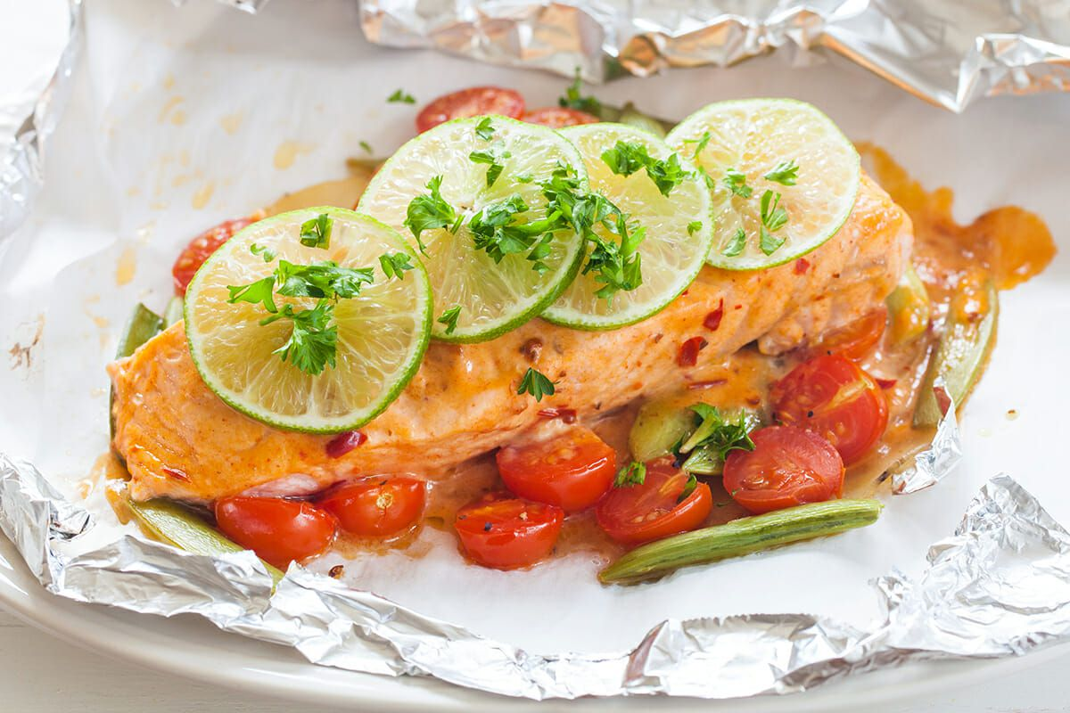 Roast salmon filet on foil with roast grape tomatoes, chopped cilantro and thinkly sliced lime on top.