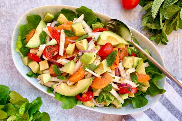 Overhead view of a summer citrus and avocado salad in a serving bowl. Mint and lettuce are also in the bowl.
