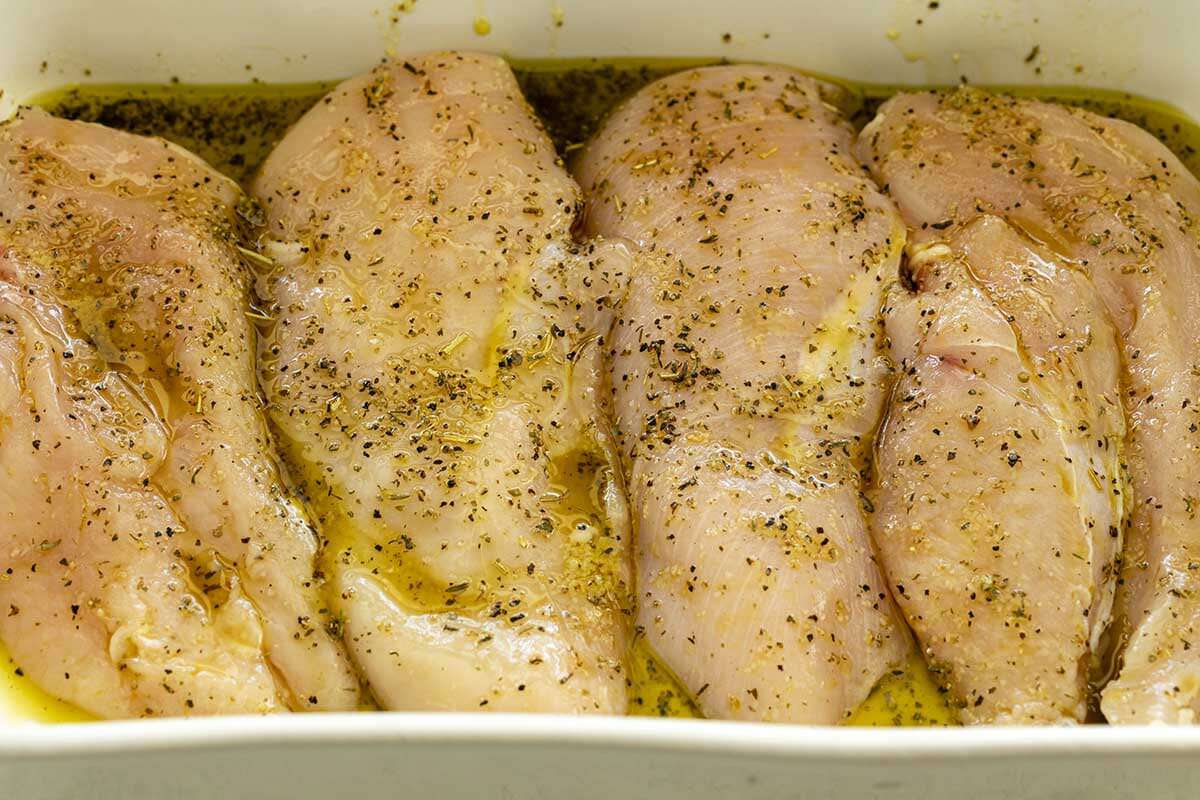 Four chicken breasts are marinating in a pan for chicken pasta skillet.