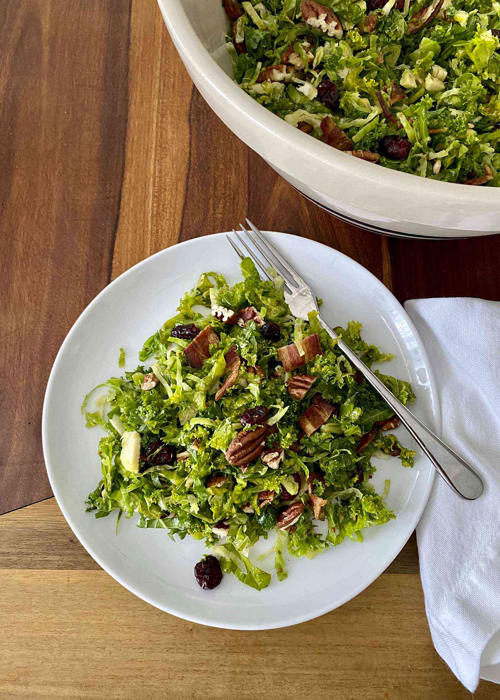 A plate and serving bowl of Raw Kale and Shaved Brussels Sprout Salad with Maple Dijon Vinaigrette.