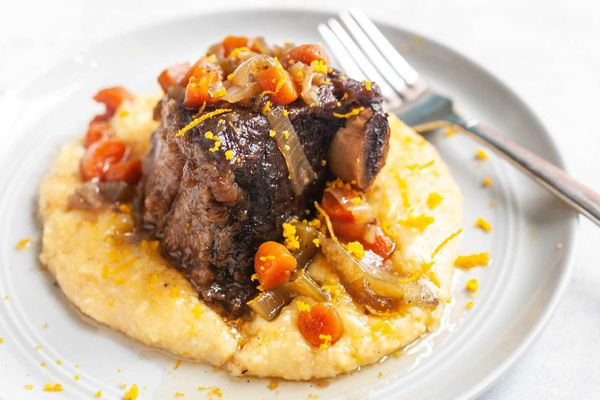 Beef Short ribs braised in the slow cooker and served with polenta on a round plate