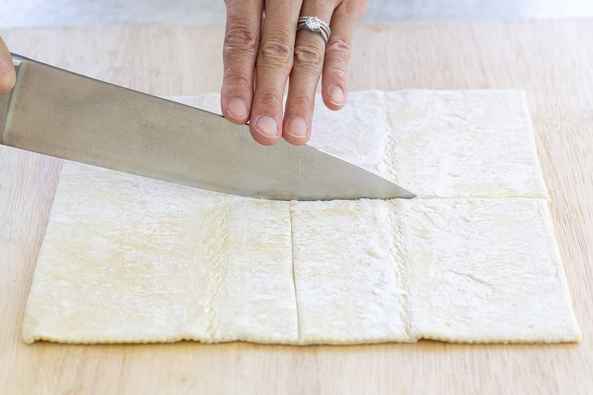 Puff pastry sheets being cut to top vegetarian pot pies.