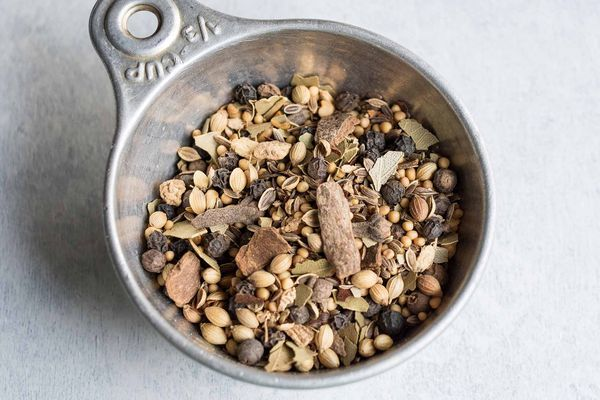 Pickling spice in a measuring cup: cinnamon, bay leaves, yellow mustard seeds, coriander seeds, black peppercorns, dill seeds, alspice berries, red pepper flakes