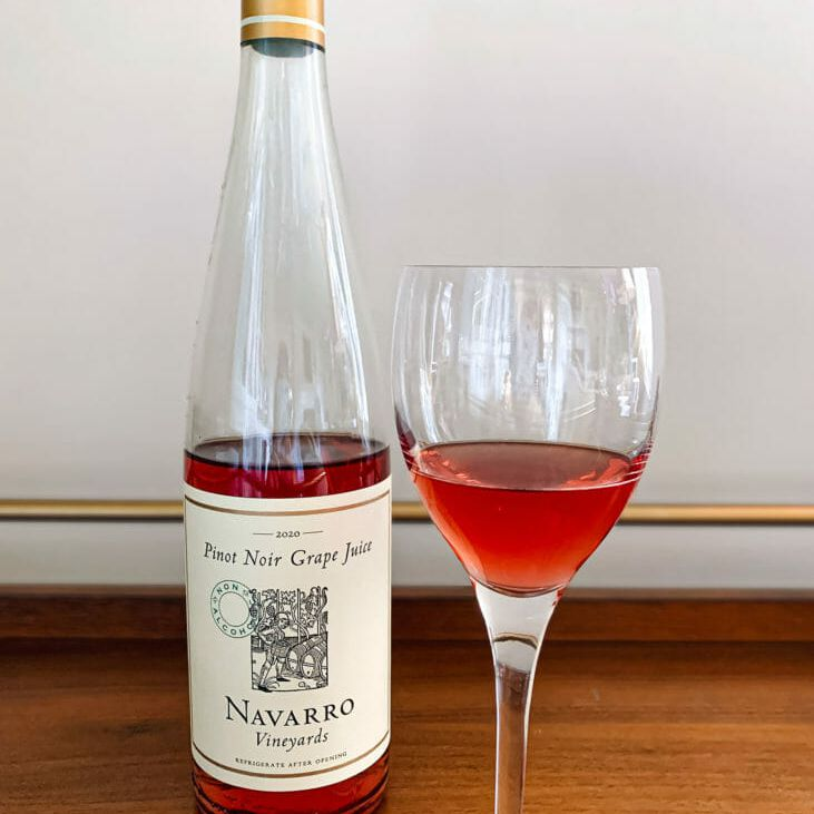 A bottle of a half empty bottle of non-alcoholic wine next to a glass of the zero proof wine.
