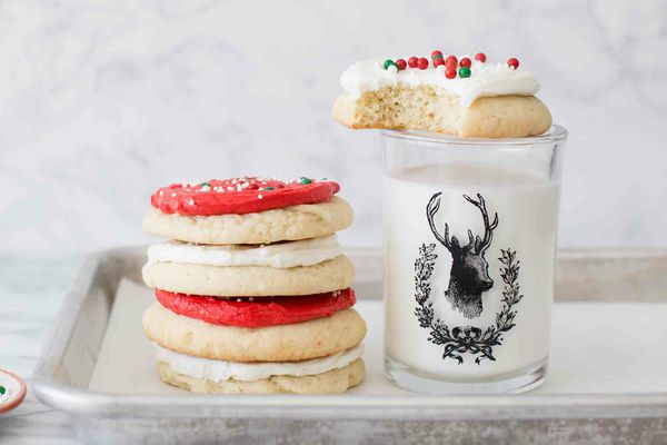 A small stack of red and white frosted cookies set next to a glass of milk.