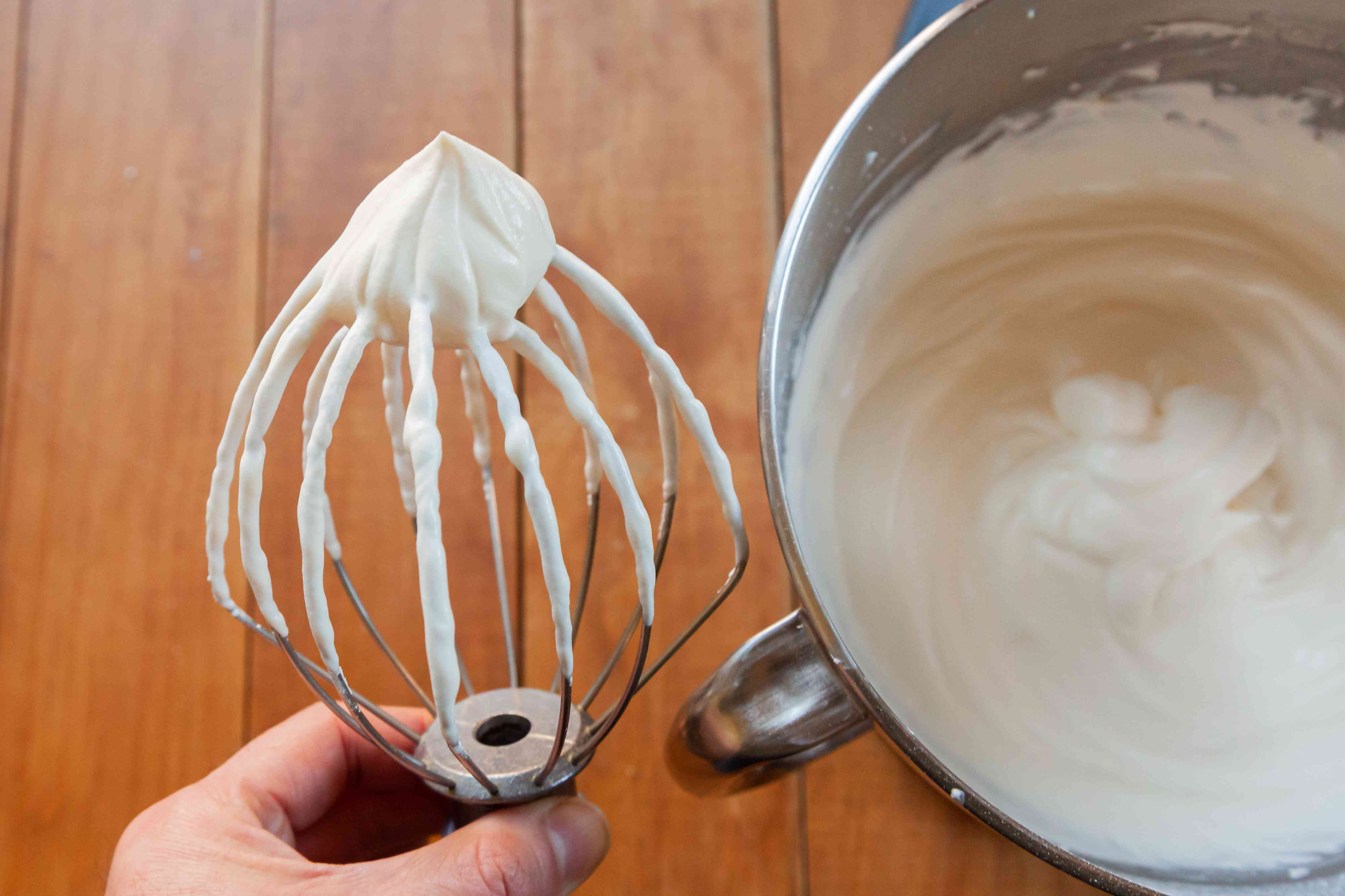Whipped cream frosting with cream cheese in a mixer bowl and a person holding the whisk attachment next to the bowl.
