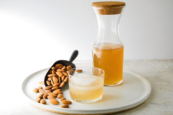 Homemade orgeat in a pitcher behind a cocktail and a scoop with almonds.