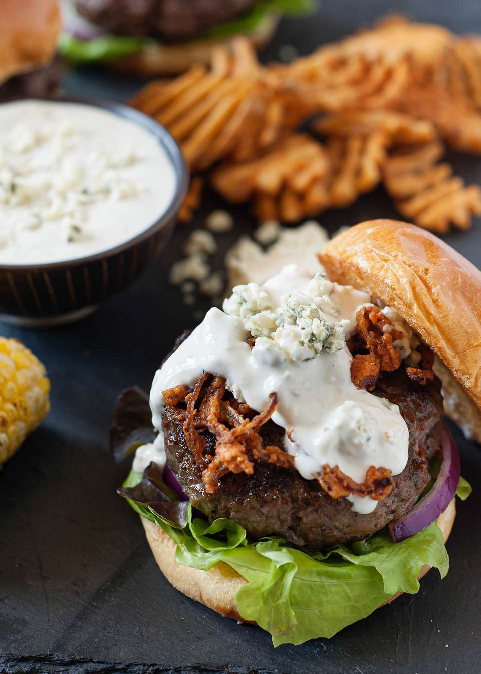 Best Burger Toppings - blue cheese sauce on a hamburger with fries in the background