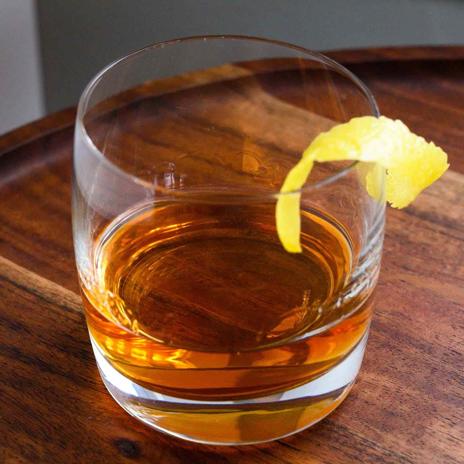 Vertical picture of sazarec drink on a round wooden table with a lemon peel on the edge of the glass.