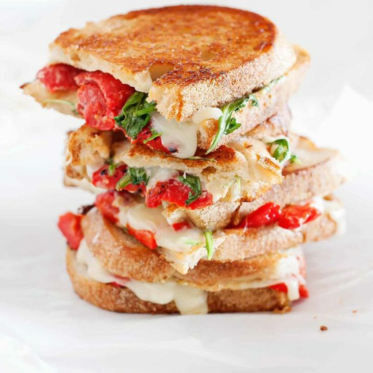 Grilled Cheese, Roasted Red Peppers, and arugula sandwiches on a white plate