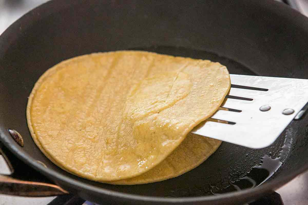 Stack corn tortillas to absorb excess oil for homemade chicken enchiladas