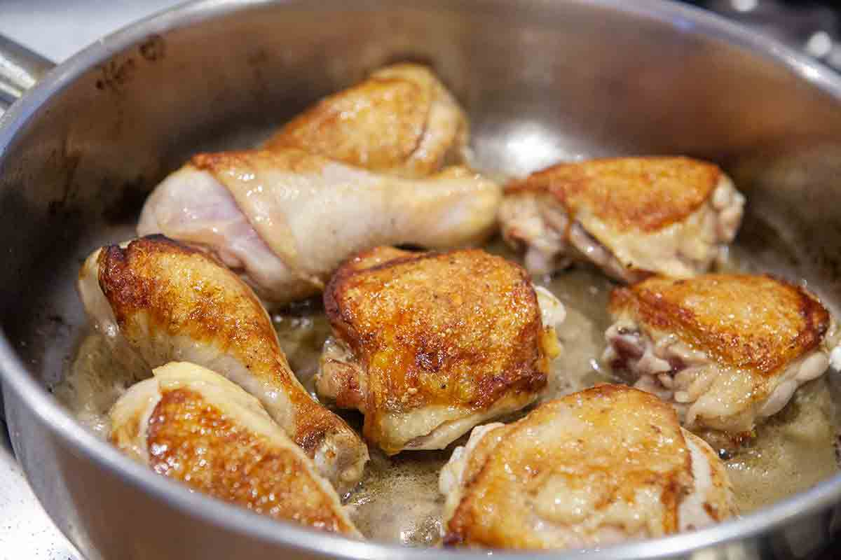 browned chicken pieces in pan