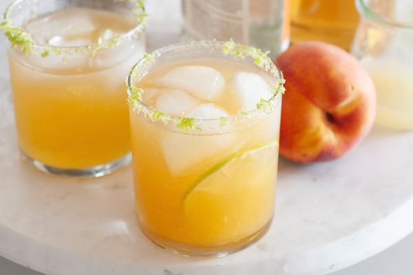 Two summery peach margaritas on a white tray with a whole peach next to it.