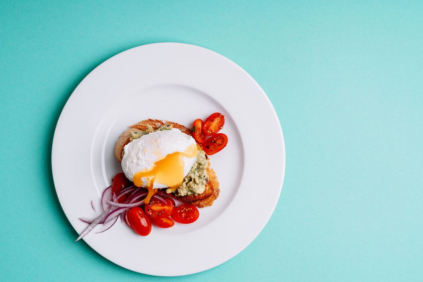 Grilled bread with avocado cream and poached egg in ceramic bowl