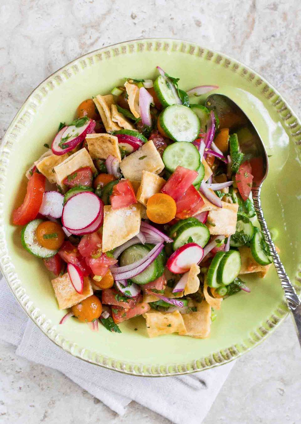 Fattoush made with baked pita chips, tomatoes, radishes, cucumbers, and a zesty vinaigrette in a round bowl