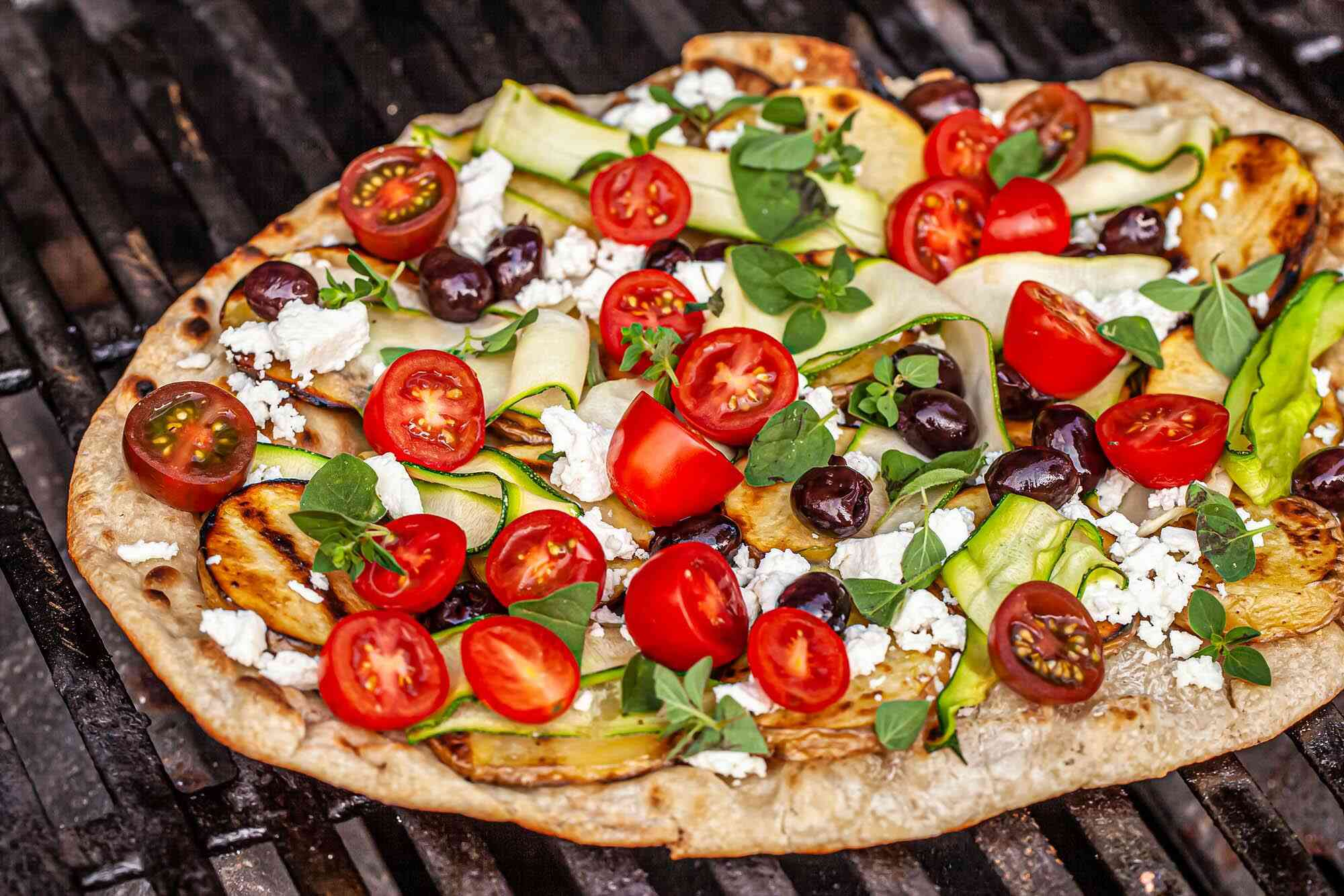 Grilled greek pizza on a grill and topped with halved tomatoes, black olives, cheese, zucchini ribbons and sliced potatoes.
