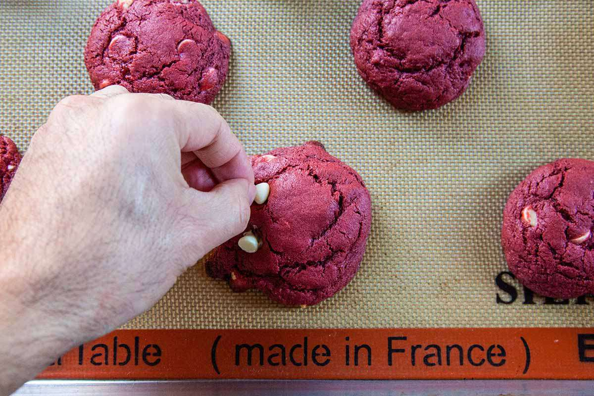 Red Velvet Cheesecake Cookies top the cookies with more chips