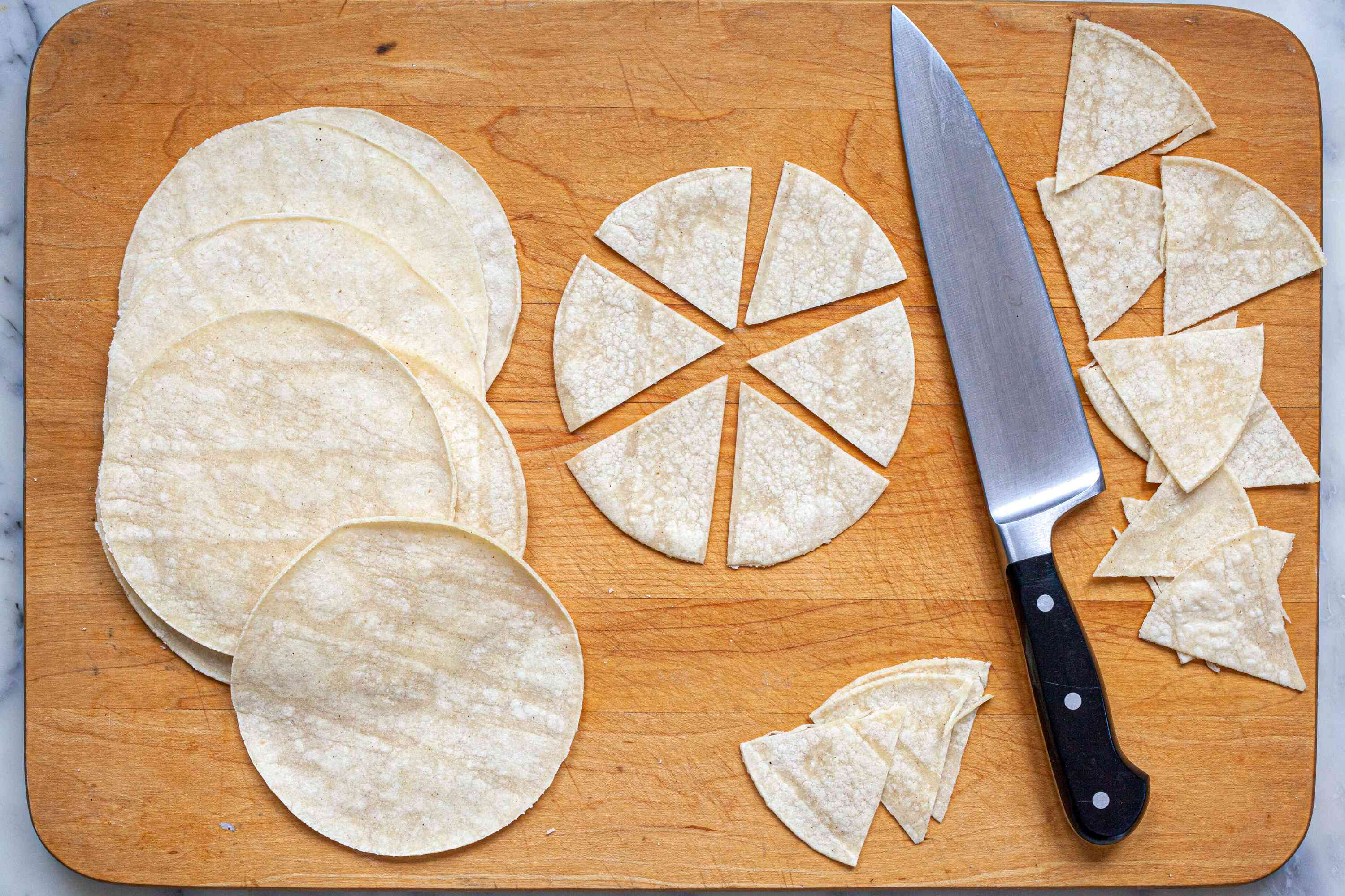 Cutting tortillas into wedges to make homemade tortilla chips.
