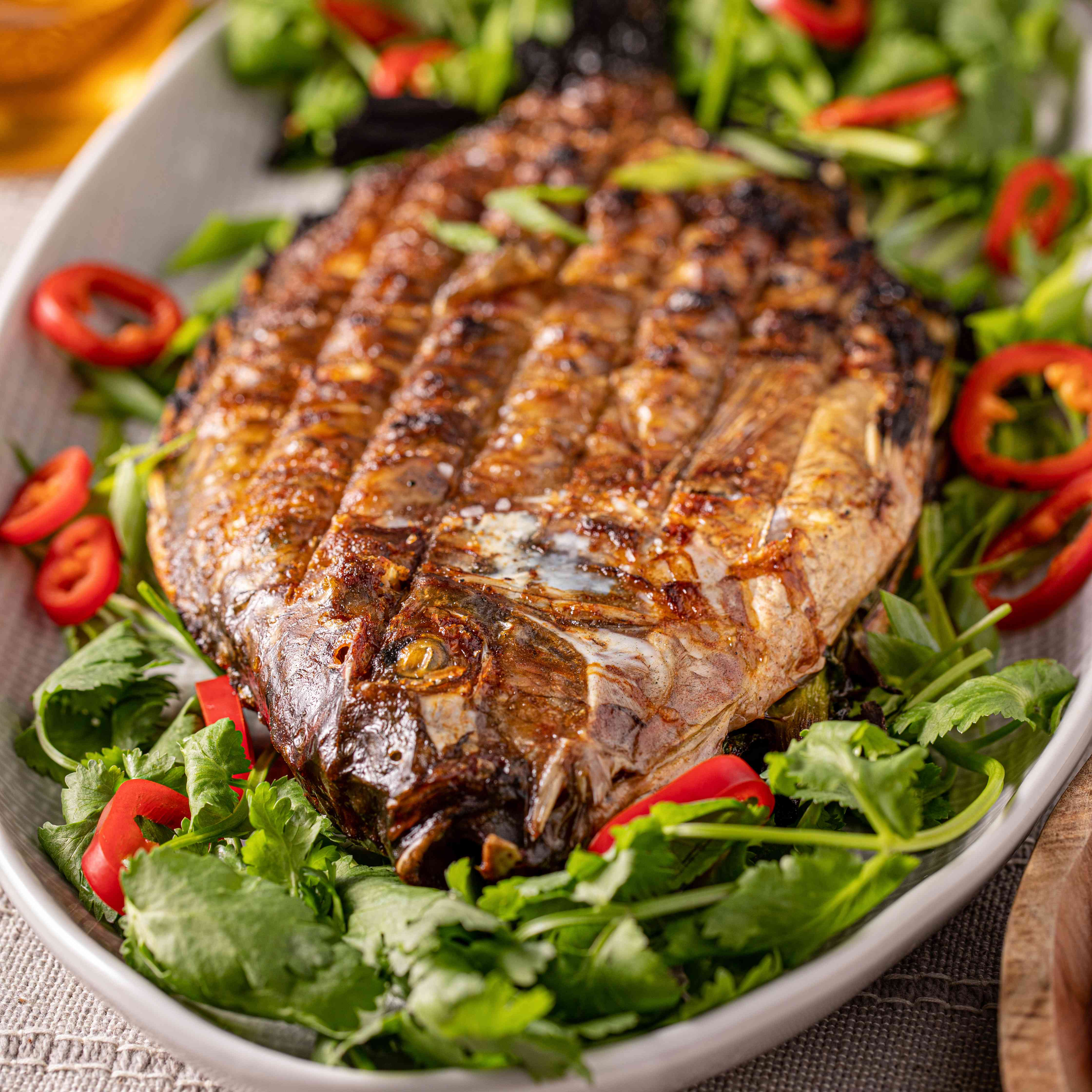 Whole fish stuffed with herbs and chilies served on a bed of lettuce.