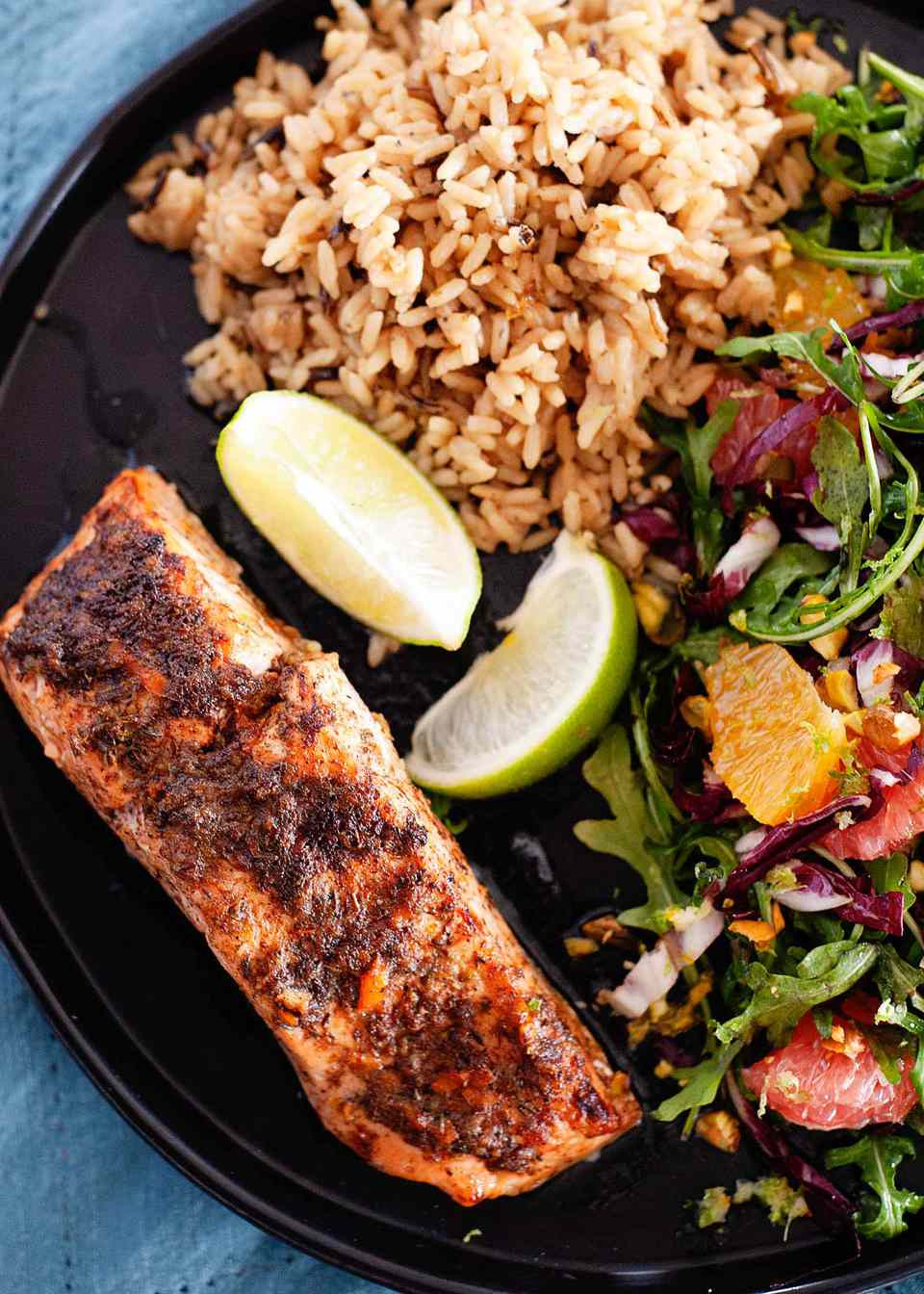 A black plate has a blackened fillet of jerk salmon on the lower left corner. Two lime wedges, red rice and a mixed green salad with citrus is also on the plate. The plate is on a blue linen.