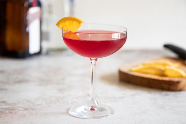 Side view of a Autumn-spiced cosmopolitan garnished with an orange wedge.