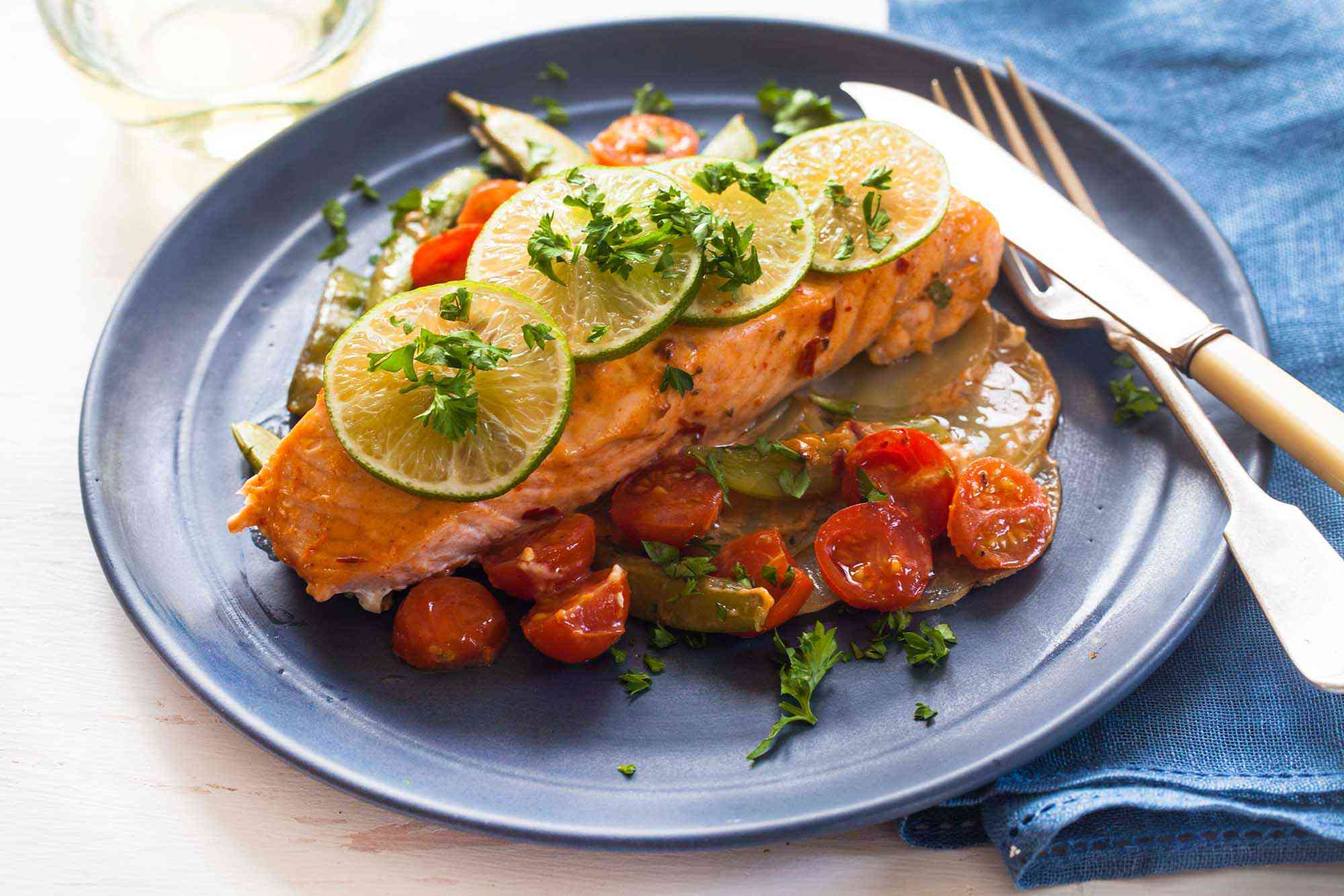 Side view of the best roasted salmon fillet. Halved grape tomatoes, chopped cilantro and thinly sliced lemon sit on top. A knife and fork are on the right side of the plate and a blue napkin is folded next to the utensils.