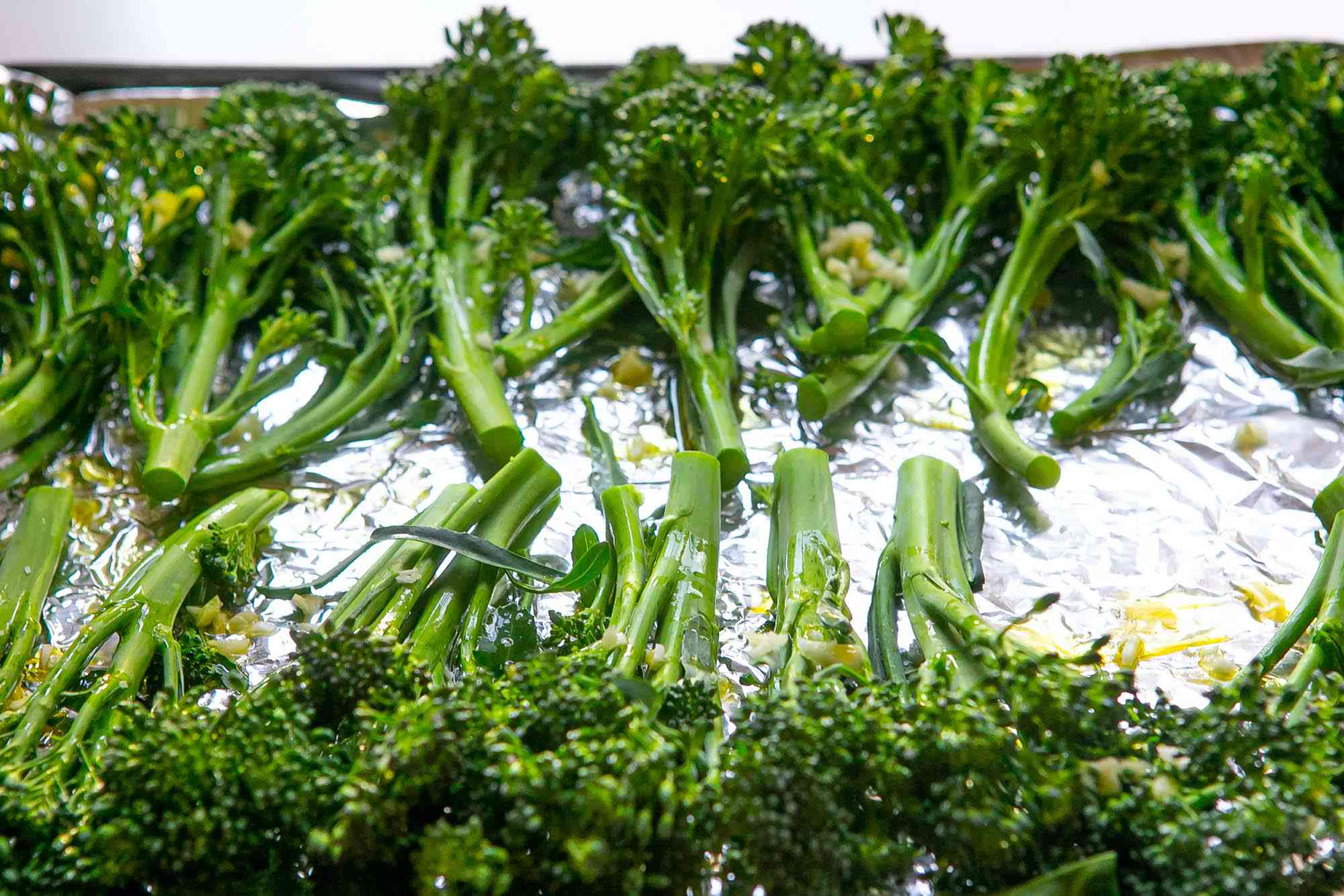 A baking sheet filled with broccolini to show how to cook broccolini.