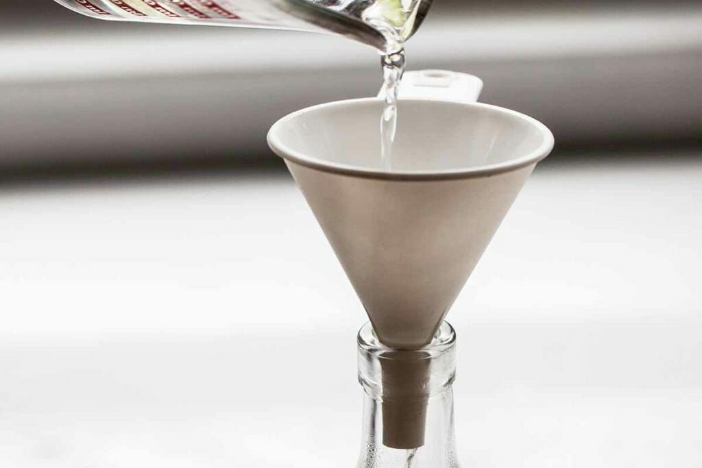 Pour simple syrup through funnel and into a bottle