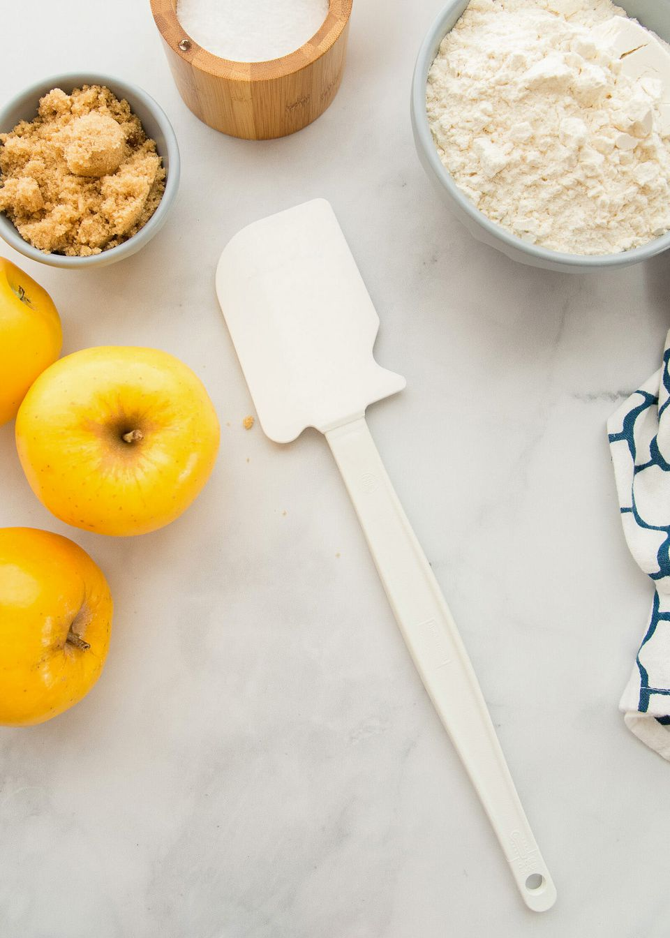 The best rubber spatula set in the center of a counter with ingredients around it.