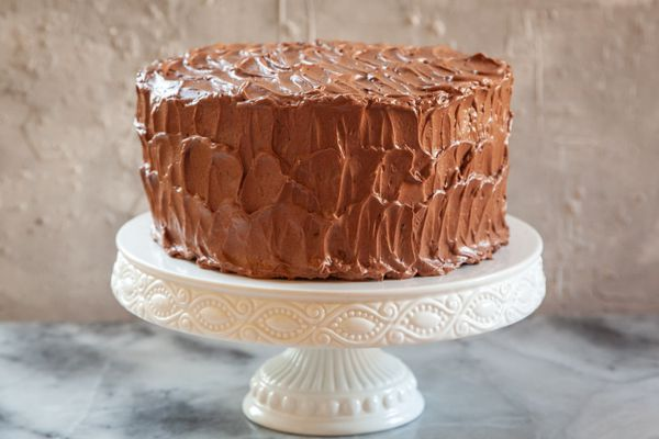 Decorated chocolate cake on a white cake stand